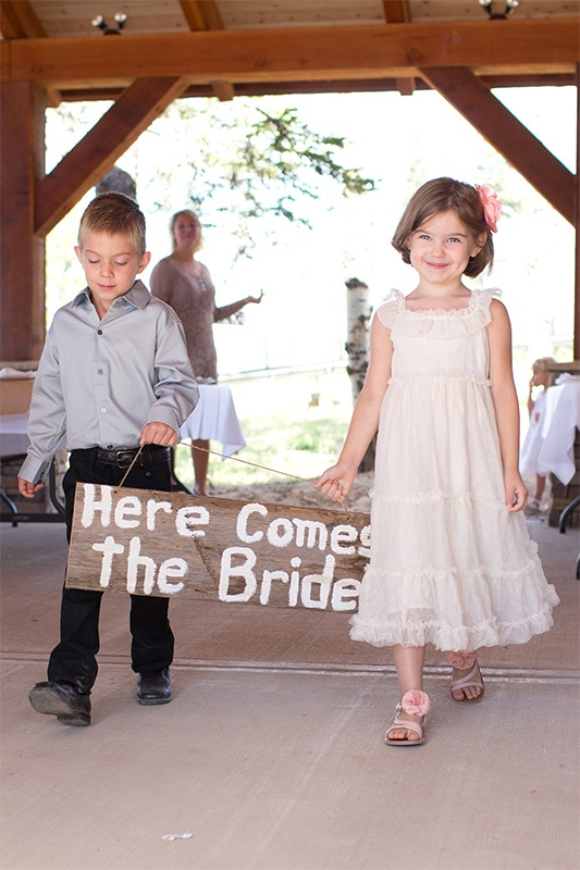A young boy and girl carry a sign that says here comes the bride.