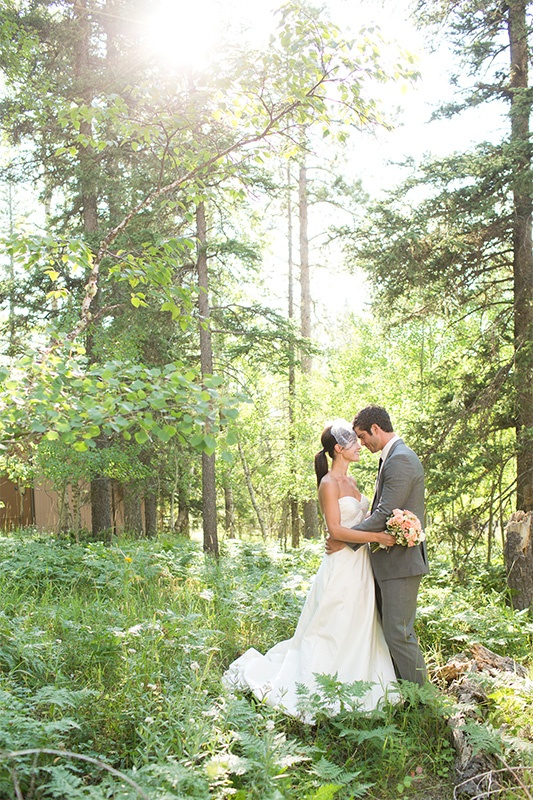 Newlywed couple hold hands in a forest.